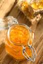 Orange jam in swing top jar on wood with on bread in the back photographed with natural light selective focus focus on Royalty Free Stock Images