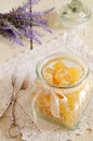 Orange jellies and lavender bunch homemade sugared in glass jar on vintage lace doily Stock Image