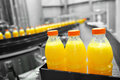 Orange juice factory bottles on assembly line Stock Image