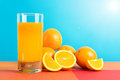 Orange juice glass of with oranges fruit against blue background Stock Image