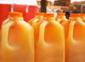 Orange juice jugs many of set up on a catering table at an outdoor event Royalty Free Stock Images