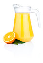 Orange juice in pitcher, half oranges and leaves Royalty Free Stock Photo