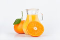 Orange juice in pitcher and oranges Royalty Free Stock Image