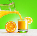 Orange juice pouring from jug into a glass green background Stock Images