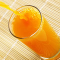 Orange juice pouring over placement Royalty Free Stock Photography
