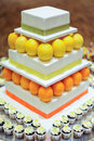 Orange lemon tier white wedding cake with mini cupcakes Stock Image