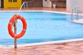 Orange life buoy hanging near swimming pool Royalty Free Stock Photo