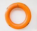 Orange life buoy hanging on the wall. Royalty Free Stock Photo