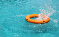 Orange life buoy splash water in the blue swimming pool Royalty Free Stock Photo