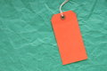 Orange luggage tag on green paper a background of crumpled paper with room for your text Stock Images