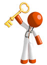 Orange man doctor holding up key to success isolated on white Royalty Free Stock Images