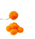 Orange mandarin tangerine on fork over white Royalty Free Stock Photography