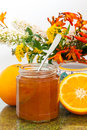 Orange marmalade with flowers jar of spoon on table surrounded by whole and cut oranges and vase of garden Royalty Free Stock Photo