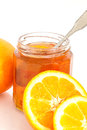 Orange marmalade jar of with spoon surrounded by whole and cut oranges Royalty Free Stock Images