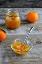 Orange marmalade in a jar with spoon whole oranges on wooden background Stock Images