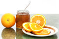 Orange marmalade and oranges slices in a jar set on a kitchen table Stock Photo