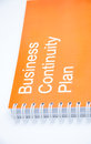 Orange notebook on a white backround small with inscription business continuity plan Royalty Free Stock Photos