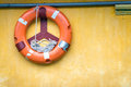 Orange old lifebuoy with rope attached to wall yellow buoy on it inside equipment for rescue of people precaution for survival in Stock Photo