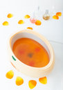 Orange paraffin wax in bowl manicure in beauty spa salon and petals and skincare Royalty Free Stock Photo