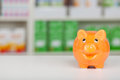 Orange piggy bank on pharmacy counter standing Stock Photos