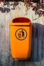 Orange plastic dust bin on the wooden wall Stock Images