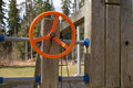Orange playground steering wheel on a wood children s equipment with a tree background Stock Photography
