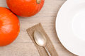 Orange pumpkins and plate with spoon on a wooden table Royalty Free Stock Photos