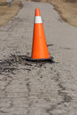 Orange pylon on damaged road showing danger a with broken asphalt Royalty Free Stock Photos