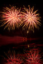 Orange and red fireworks reflected in a murky lake Stock Images