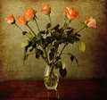Orange roses in a vase on a grunge vintage background bouquet of glass wooden table Royalty Free Stock Image