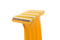 Orange safety razors with small depth of field isolated on white background Royalty Free Stock Images