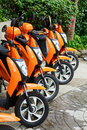 Orange scooter mototbikes parked row Royalty Free Stock Images