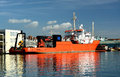 Orange ship berthed a used in the maritime wind turbine business in small dockside location Stock Image