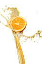 Orange slice in juice stream Stock Photos