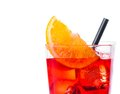 Orange slice on top of the red cocktail with ice cubes and straw on white background Royalty Free Stock Photo