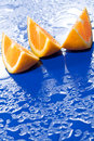 Orange slices on blue surface Royalty Free Stock Photos