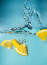 Orange slices falling into the blue water close-up, macro, splash water, bubbles, blue background Royalty Free Stock Photo