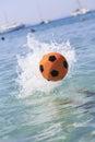 Orange Soccer Ball Splashing On The Water