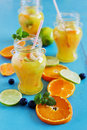 Orange soft drink and sliced citrus fruits on a blue wooden background health and diet food selective focus Stock Photography