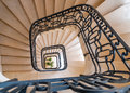 Orange spiral staircase in with metal banister down Royalty Free Stock Photo