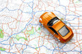 Orange sports car toy on map Royalty Free Stock Photo