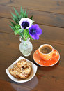 Orange spotty mug and cookies with greek coffee vase with anemones Royalty Free Stock Photography