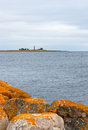 Orange stones on the coastline of gotland sweden lighthouse other shore Royalty Free Stock Photography