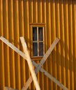 Orange structured wall with window and leant planks metal Royalty Free Stock Photo