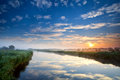 Orange sunrise over wide river with reflected blue sky Royalty Free Stock Image