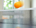 Orange table tennis ball moving over net Stock Images