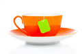 Orange tea cup and green bag isolated on white background Royalty Free Stock Image