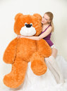 Orange teddy bear young blond woman with a big Stock Photography