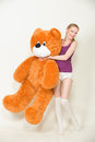 Orange teddy bear young blond woman with a big Royalty Free Stock Image