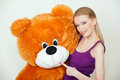 Orange teddy bear young blond woman with a big Stock Image
